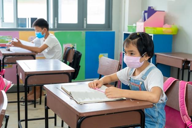Азиатские студенты нося защитную маску в элементарной комнате.