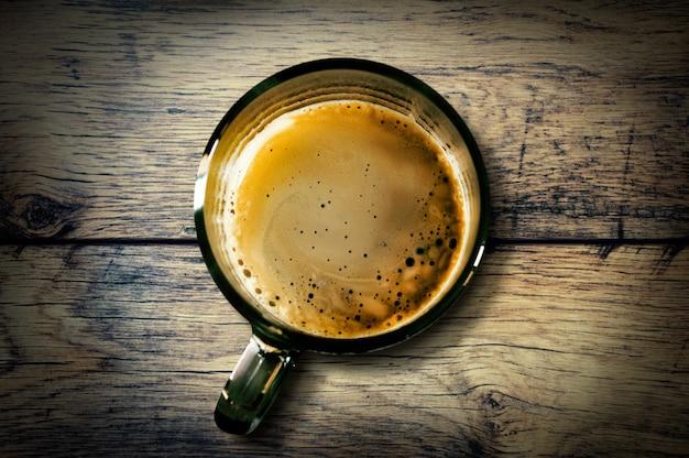 ヴィンテージの木製のテーブルの上の泡とコーヒーのカップ。上からの眺め