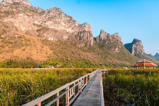 カオサムロイヨット国立公園、タイで夕暮れ時の湖と山の景観の木の橋。