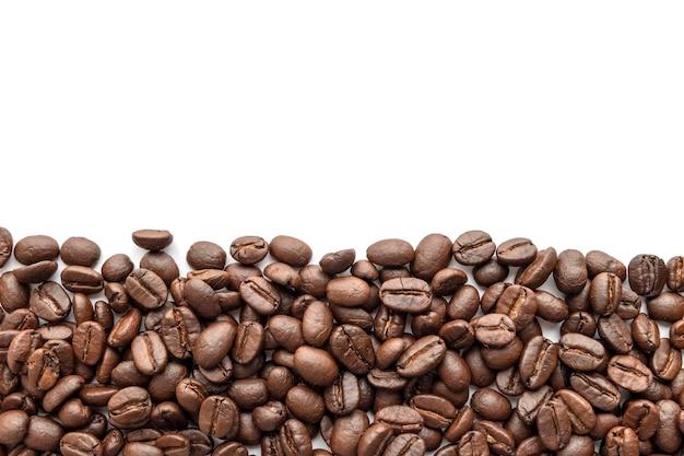 白い背景の上のコーヒー豆の焙煎。閉じる。