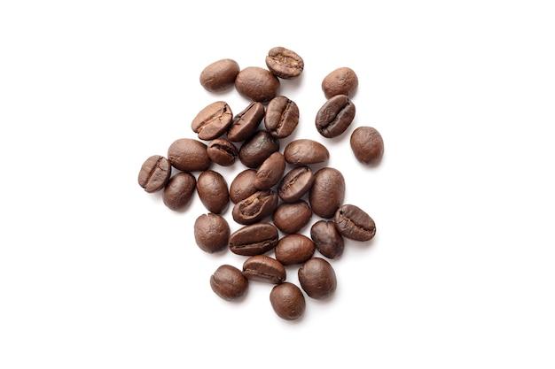 Зажаренные в духовке кофейные зерна изолированные на белой предпосылке. крупный план.