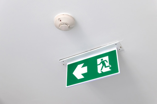 非常口非常口ドア天井の非常口ドア。方法を示す緑の非常口サイン。