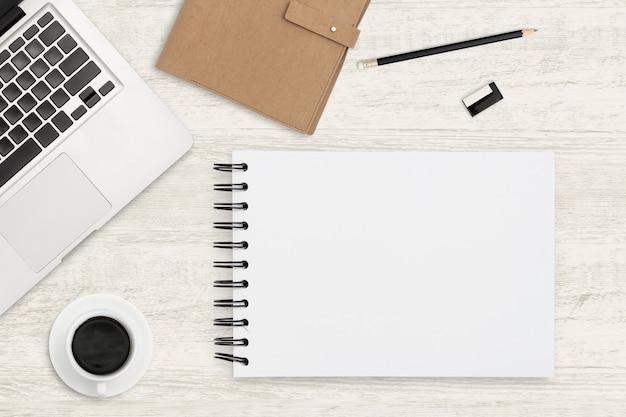 ビジネス背景の平面図作業スペース。木製の背景に空白のノートブックおよびオフィス用品。