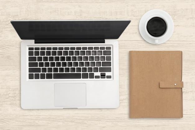 ラップトップコンピューターと木製のテーブルの空白のノートブック。