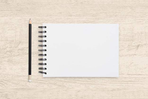 空白のノートブックとウッドテクスチャの鉛筆の平面図オブジェクト。
