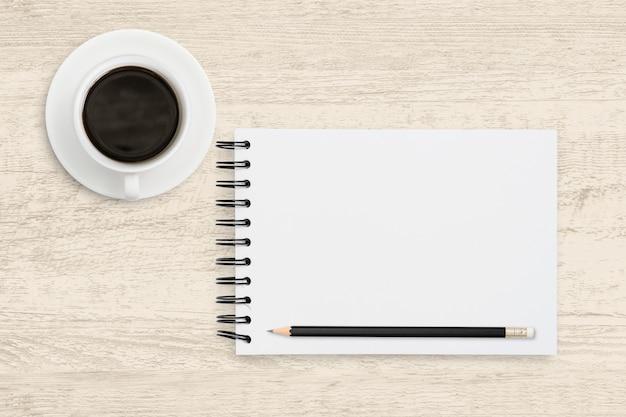 木製の質感のコーヒーカップとノートのホワイトペーパーシートの平面図ビジネス。