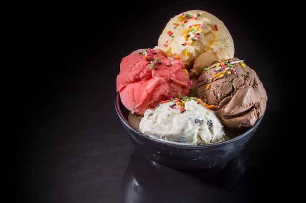 Мороженое совок в миске, смешанное мороженое в чашке с мороженым на черном фоне