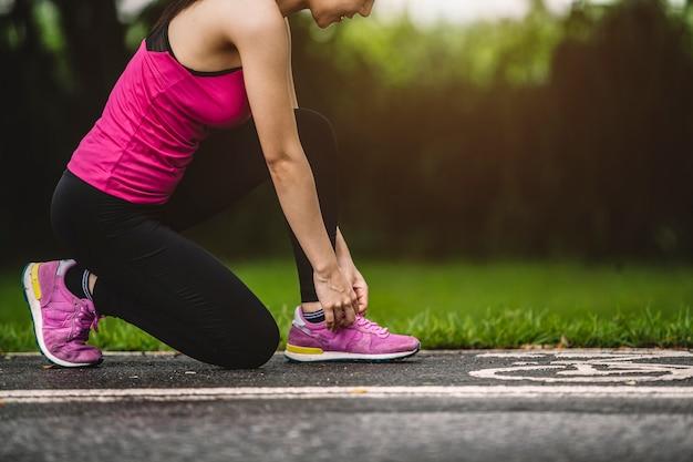 女性スポーツフィットネスランナーの森で屋外ジョギングの準備をして