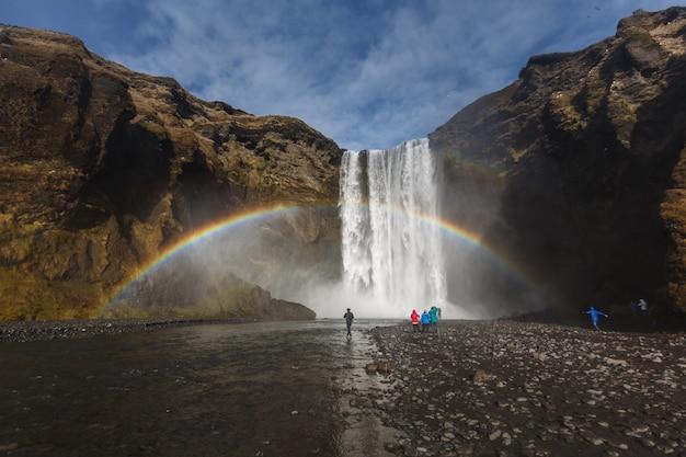 Турист на водопаде скогафосс с двойной радугой под голубым небом