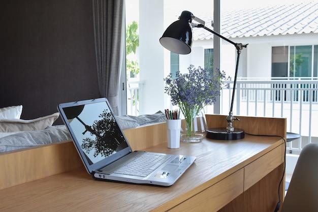 現代の作業領域でコンピュータのノートブック、鉛筆、ランプ、花の木製テーブル