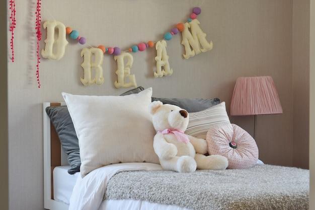 ベッドに人形と枕が置かれたモダンなキッズルーム