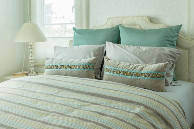 ベッドサイドテーブルに枕と読書ランプ付きの居心地の良いベッドルームインテリア