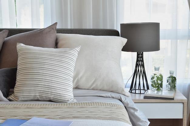 スタイリッシュなベッドルームインテリアデザイン。ベッドには茶色の模様付き枕と装飾テーブルランプが付いています。