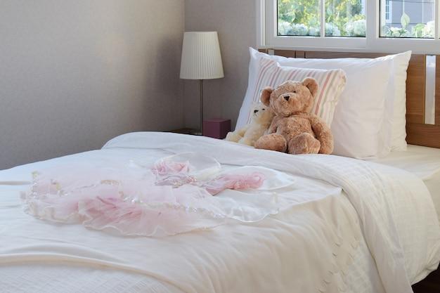 ベッドの上に枕と人形が置かれた白い寝室