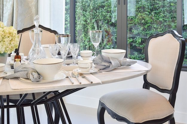 エレガントなテーブルセッティングのモダンな家庭のダイニングテーブルと快適な椅子