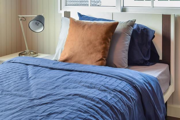 青いベッドに茶色の枕が置かれたモダンなベッドルーム