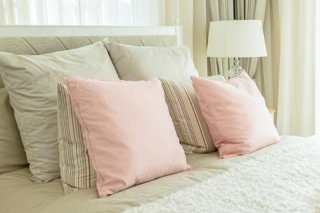 ベッドサイドのテーブルにピンクの枕と読書ランプ付きの居心地の良いベッドルームインテリア