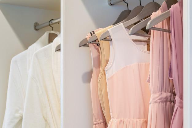 白いワードローブのコートハンガーに掛かるカラフルなドレスの行