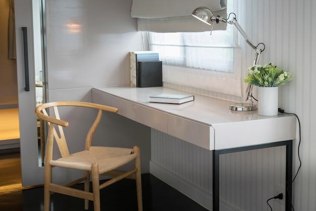 木製の椅子と家庭の現代作業エリアにある本を備えた白いテーブル