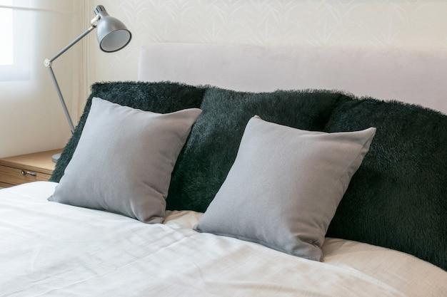 白いベッドと装飾的なテーブルランプの灰色の枕のベッドルームインテリアデザイン。