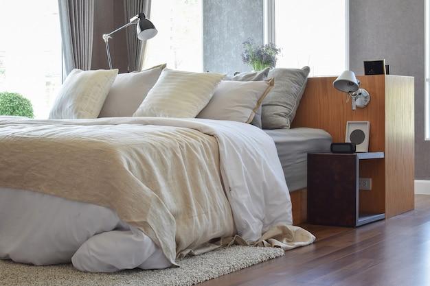スタイリッシュなベッドルームインテリアデザイン。ベッドに白い縞模様の枕と装飾的なテーブルランプが付いています。