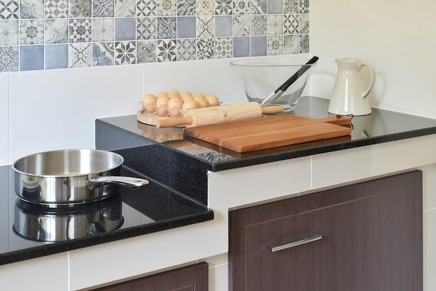 黒い花崗岩のカウンタートップに現代のセラミック製の台所用品と道具