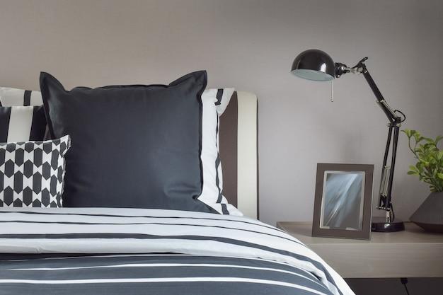 ベッドサイドテーブルに枕と読書ランプ付きのモダンなベッドルームインテリア
