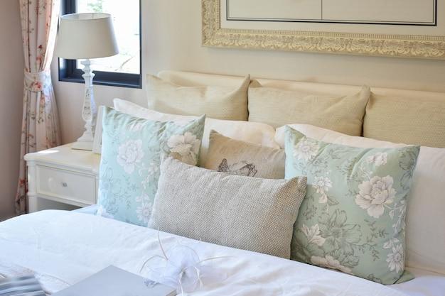 花柄の枕と白いベッドサイドテーブルの読書ランプ付きのヴィンテージのベッドルームインテリア