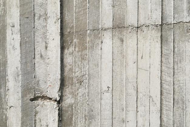 生のコンクリートの壁に打たれた木製の型枠のテクスチャ