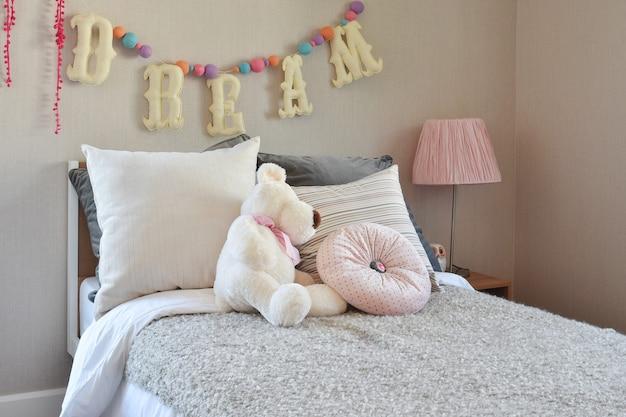 Современная детская комната с куклой и подушками на кровати