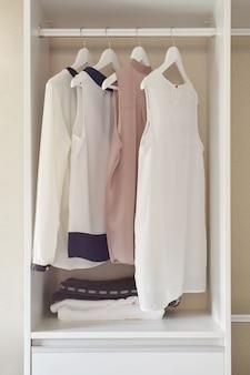 白いワードローブのコートハンガーに掛かっているドレスの行