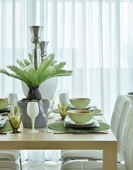 ダイニングテーブルの上の緑色の配色設定で美しいモダンなセラミック食器