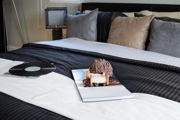 本、かぎ針編み、グラムで装飾的なモダンなブラックトーンのベッドルーム