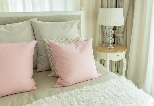 ピンクの枕とベッドサイドテーブルの上の読書ランプ付きの居心地の良いベッドルームのインテリア