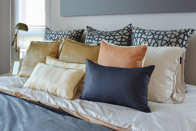 ベッドの上にオレンジとゴールドの枕とモダンなベッドルームのインテリアと