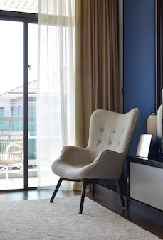 モダンなベッドルームのインテリアのカーペットの上の快適な椅子
