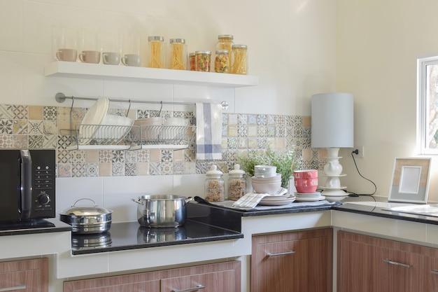 モダンなセラミックの台所用品と黒御影石のカウンタートップの上の道具