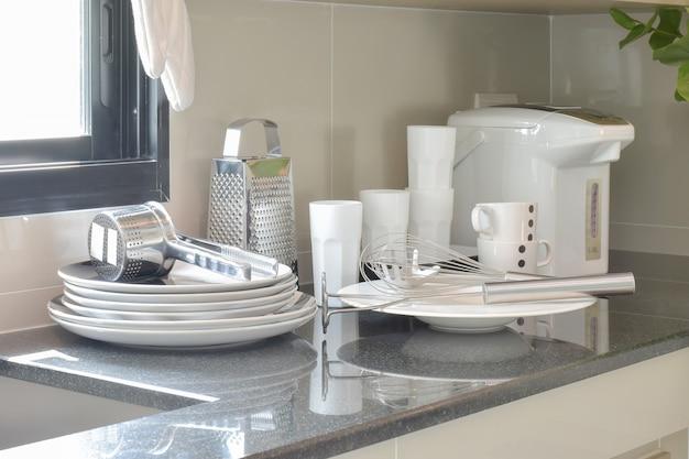 カウンターの上の白いセラミックセットとステンレスの台所用品