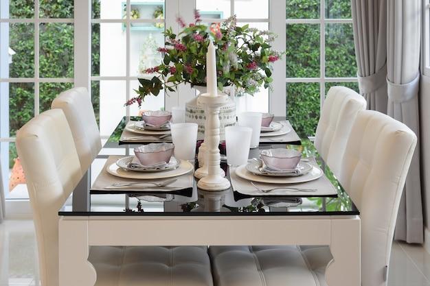 ダイニングテーブルとエレガントなテーブルセッティングのビンテージスタイルの快適な椅子