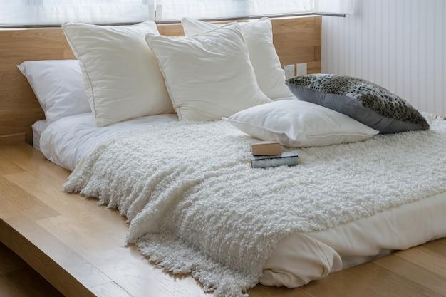 ベッドの上の黒と白の枕とスタイリッシュなベッドルームのインテリアデザイン。