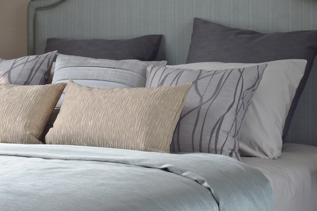テクスチャとライトブルーのサテンの毛布が付いているベッドの上のパターンの枕
