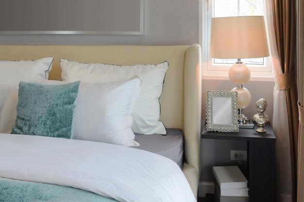 白いベッドと装飾的なテーブルランプの上の白と緑の枕の寝室のインテリアデザイン。