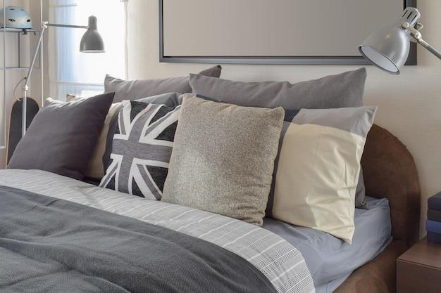 灰色の枕と自宅の木製のベッドサイドテーブルの上のランプのモダンなベッドルーム