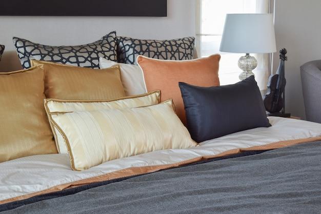 Современный интерьер спальни с оранжевыми и золотыми подушками на кровати и прикроватной тумбочке