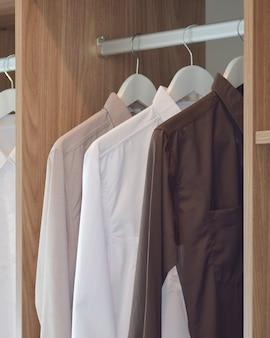 木製のワードローブにぶら下がっている古典的な色のシャツ