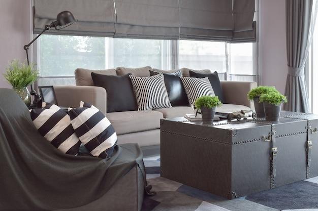 モダンなインダストリアルスタイルのリビングルームのソファーに縞模様と黒革の枕