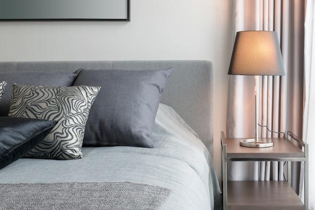 ベッドの上の黒い模様の枕と装飾的なテーブルランプでスタイリッシュな寝室のインテリアデザイン。