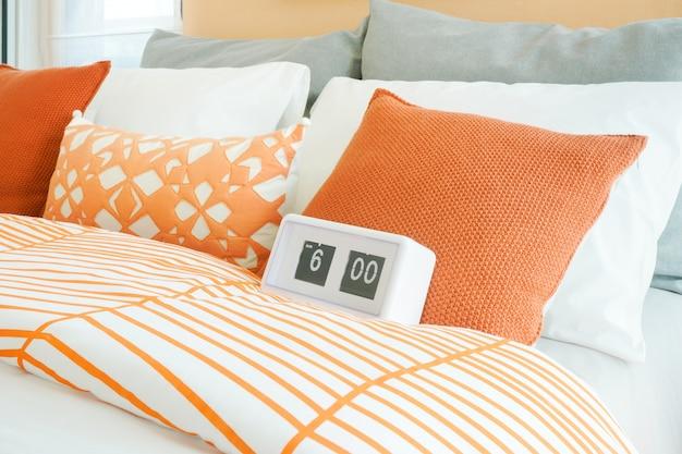バックにオレンジ、白、灰色の枕が付いたベッドの白い目覚まし時計