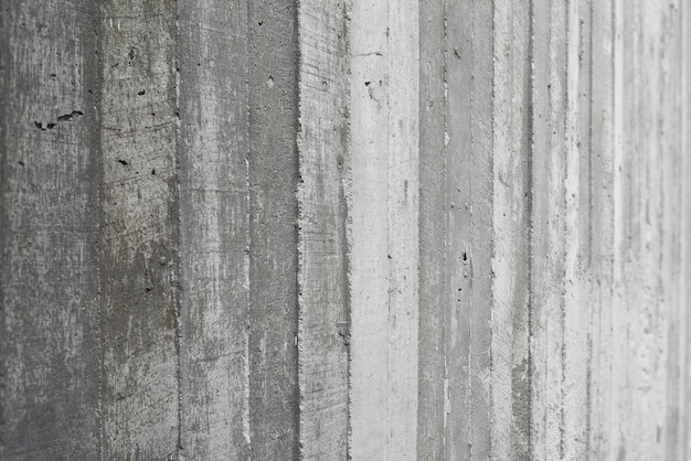 生のコンクリートの壁に打ち抜かれた木製の作品のテクスチャ