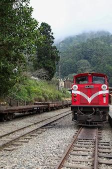 Старый красный поезд на линии алишан (скоростной спуск) возвращается в железнодорожную станцию чийи в туманный день.